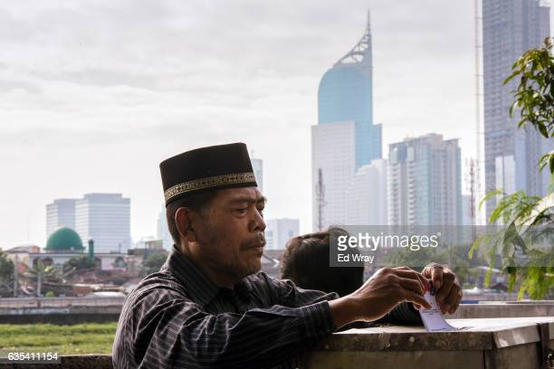 An Indonesian man casts his ballot in the governor's election at a polling station on February 15 2017 in Jakarta Indonesia Residents of Indonesia's...