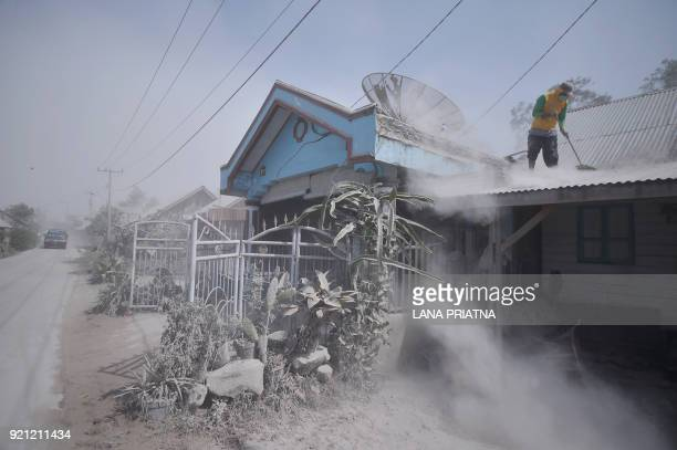 TOPSHOT An Indonesian man cleans dust from a roof of a house after Mount Sinabung spewed volcanic ash a day before in Karo North Sumatra on February...