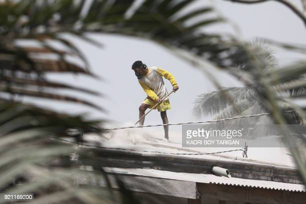 TOPSHOT An Indonesian man cleans volcanic ash from a roof of a house after Mount Sinabung volcano spewed thick volcanic ash across the area the day...