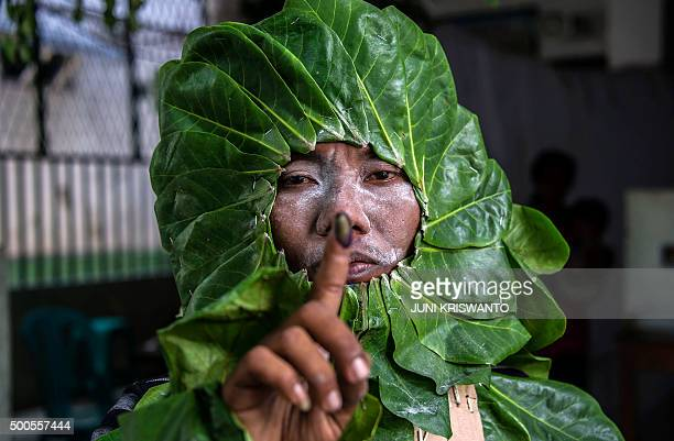 TOPSHOT An Indonesian man dressed up as a plant to increase peoples' awareness of the environment shows his inked finger after voting in the...