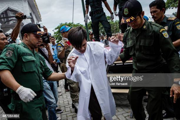 An indonesian man escorted by the sharia police after get caning in public from an executor known as 'algojo' for having gay sex which is against...