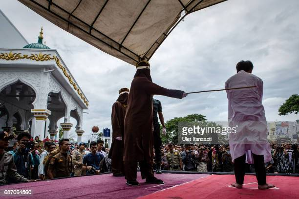 An Indonesian man gets caning in public from an executor known as 'algojo' for having gay sex, which is against Sharia law at Syuhada mosque on May...