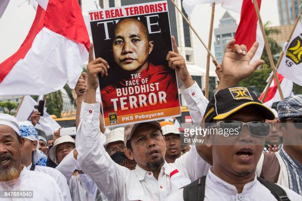 An Indonesian man holding up a poster depicting Myanmar monk Wirantu demonstrates with thousands of Indonesian Muslims in support of the Rohingya...