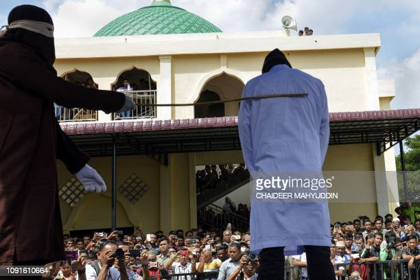 An Indonesian man is caned in public in Banda Aceh on January 31 as punishment for being caught cuddling with his girlfriend Two teenagers were...