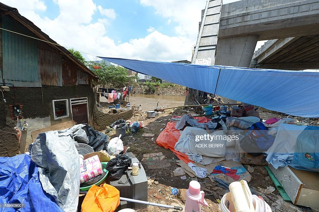 An Indonesian man lies down in a makeshift tent next to the Ciliwung river following heavy floods in Jakarta on January 23, 2013