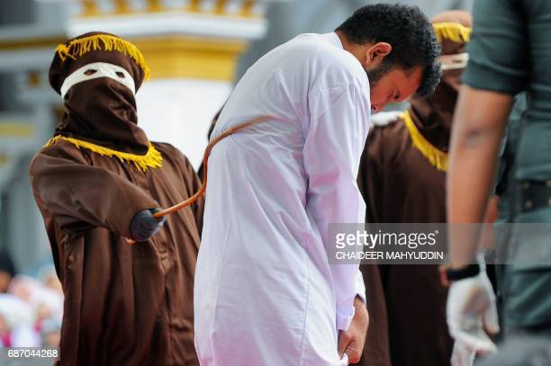 TOPSHOT An Indonesian man one of two to be publicly caned for having sex is caned in Banda Aceh on May 23 2017 The pair aged 20 and 23 were found...