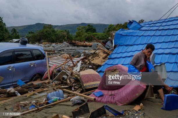 An Indonesian man sits on the rubble of a destroyed home in a neighborhood which was largely demolished by recent flash floods on March 19 2019 in...