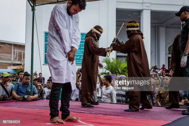 An indonesian man stands as prepare get caning in public from an executor known as 'algojo' for having gay sex which is against Sharia law at Syuhada...