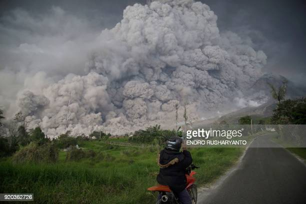 TOPSHOT An Indonesian man takes picture of Mount Sinabung volcano as it spews thick volcanic ash into the air in Karo North Sumatra on February 19...