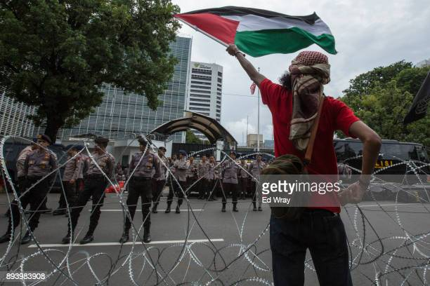 An Indonesian man waves a Palestinian flag at the US embassy at a large demonstration against the United States' decision to recognize Jerusalem as...