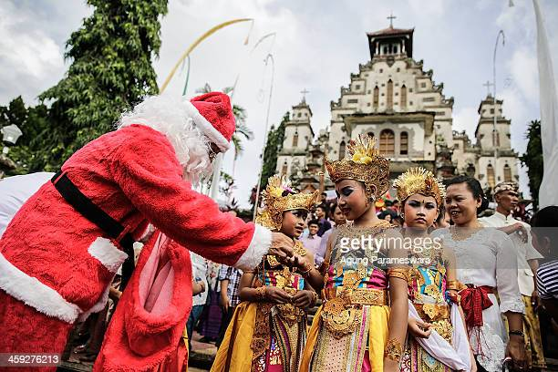 An Indonesian man wearing a Santa Claus costume hands a gift to a dancer during Christmas celebrations at Hati Kudus Yesus Church on December 25 2013...