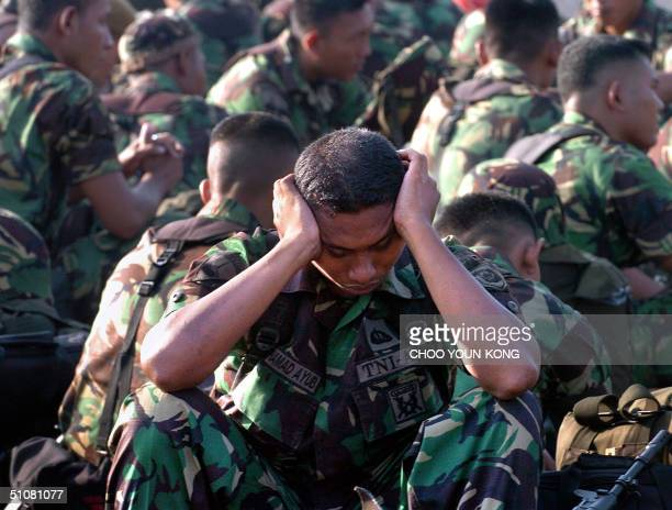An Indonesian marine hangs his head as the troops wait to leave their base for conflict province Aceh in south Jakarta 19 July 2004 The military...