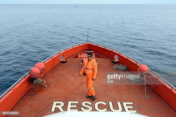 An Indonesian member of a search and rescue team looks on during the search for victims who were on board a boat carrying more than 100 people that...