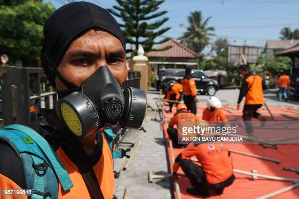 An Indonesian member of a Search and Rescue team wears a mask as they build a temporary shelter for people in Sleman on May 11 after after mount...