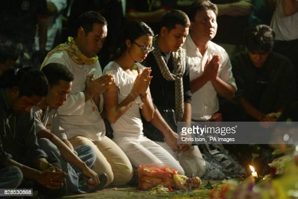 An Indonesian men and women pray as an eerie silence falls over the normally bustling Legian Street in Kuta Bali at 1130pm exactly one week on from...