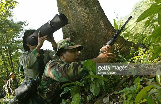 An Indonesian military personnel teaches journalists how to use trees as protection in war coverage during a media training exercise June 9 2003 at...