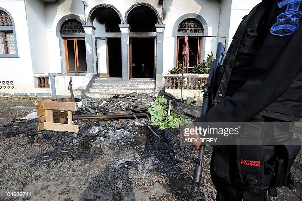 An Indonesian Mobile Brigade policeman inspects a damaged mosque in Cisalada village Bogor on October 2 after a group of people attacked a village...