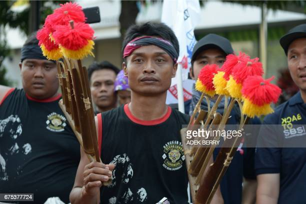 An Indonesian musician plays a traditional bamboo percussion instrument called 'angklung' during a May Day protest in Jakarta on May 1 2017 Millions...