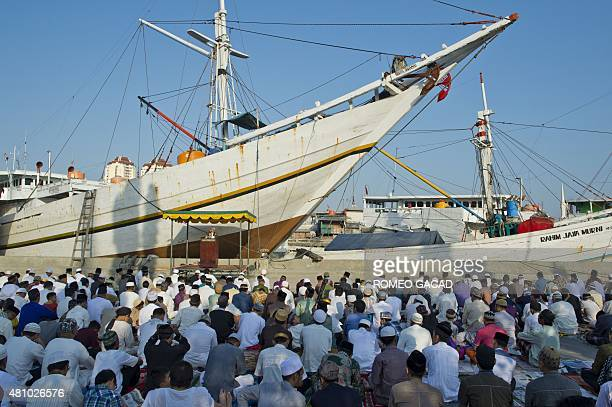 An Indonesian Muslim cleric delivers his sermon next to a traditional cargo and fishing boat during Eid al-Fitr celebrations at the Sunda Kelapa port...