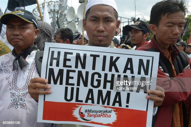 CORRECTION An Indonesian Muslim man holds a placard that reads stop insulting clerics during a rally at the National Monument in Jakarta on February...