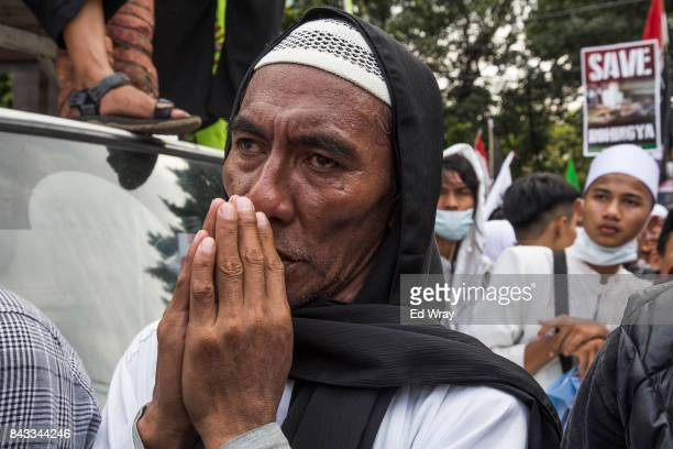 An Indonesian Muslim man prays as thousands of members of various Indonesian muslim groups demonstrate in support of Myanmar's Rohingya population in...