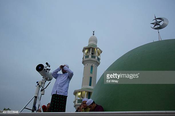 An Indonesian Muslim man tries to sight the new moon the sign of the start of the Islamic holy month Ramadan from the top of a mosque on June 27 2014...