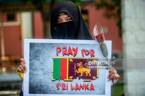 An Indonesian Muslim student shows her solidarity to the victims of the Sri Lankan blasts, in Surabaya on April 22, 2019. - Sri Lanka said it...