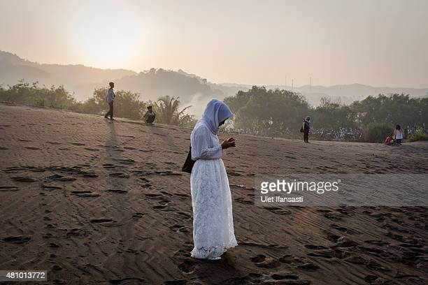 An Indonesian muslim woman attends Eid AlFitr prayer on 'sea of sands' at Parangkusumo beach on July 17 2015 in Yogyakarta Indonesia Eid AlFitr marks...
