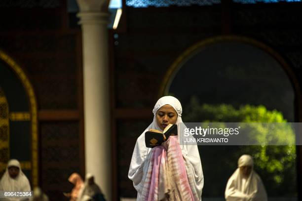 An Indonesian Muslim woman offers prayers and read the Koran on the 21st day of holy month of Ramadan at a Al Akbar mosque in Surabaya early on June...