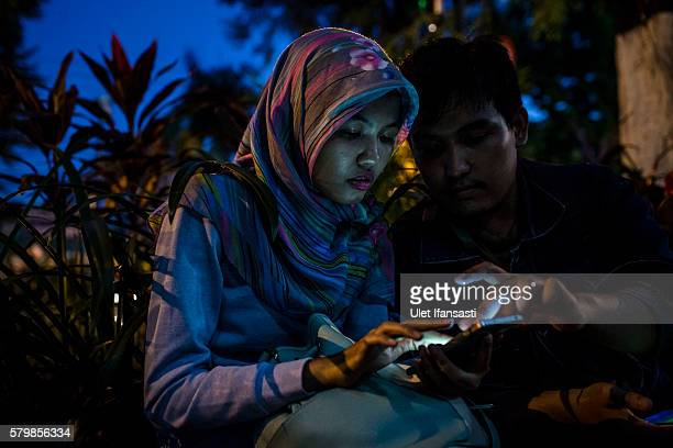 An Indonesian Muslim woman Raditya plays Pokemon Go game on her smartphone on July 24 2016 in Yogyakarta Indonesia Pokemon Go which uses Google Maps...