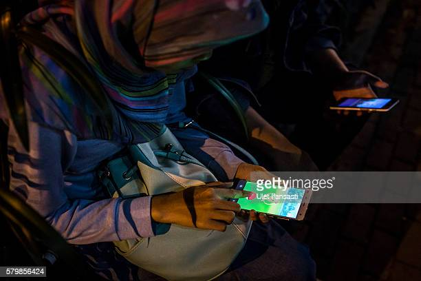 An Indonesian Muslim woman Raditya plays Pokemon Go game on her smartphone on July 24 2016 in Yogyakarta Indonesia 'Pokemon Go' which uses Google...