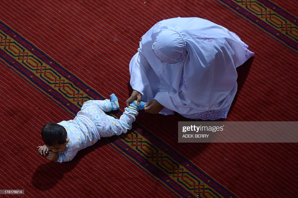 An Indonesian Muslim woman tends to a toddler during prayers on the first night of the holy month of Ramadan at the Istiqlal mosque in Jakarta on July 9, 2013. Islam's holy month of Ramadan is celebrated by Muslims worldwide marked by fasting, abstaining from foods, sex and smoking from dawn to dusk for soul cleansing and strengthening the spiritual bond between them and the Almighty.