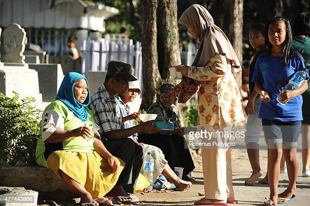 An Indonesian Muslims gives donation to the beggars as she make pilgrimages to the graves of family members before Ramadan on June 17 2015 in...