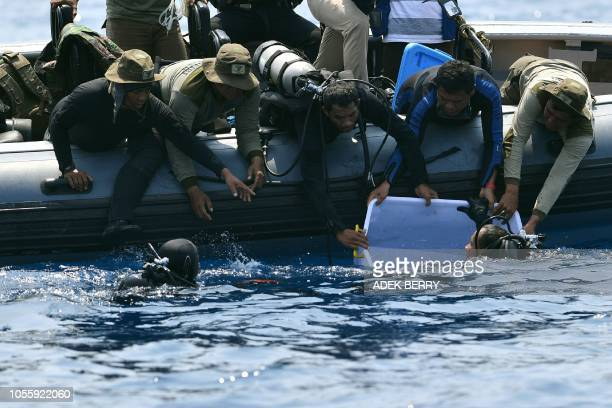 TOPSHOT An Indonesian Navy diver holds a recovered black box under water before putting it into a plastic container after its discovery during search...