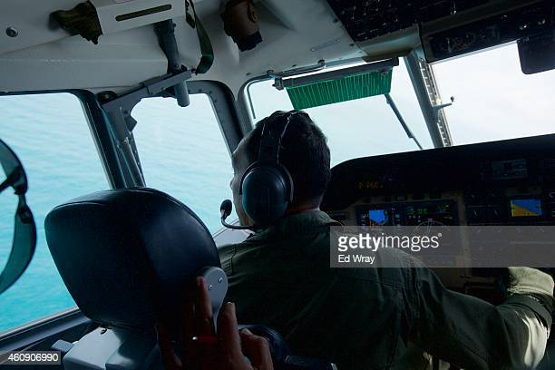 An Indonesian Navy Pilot looks out the cockpit window as he banks to check out an object sighted during a search of the waters near Bangka Island for...