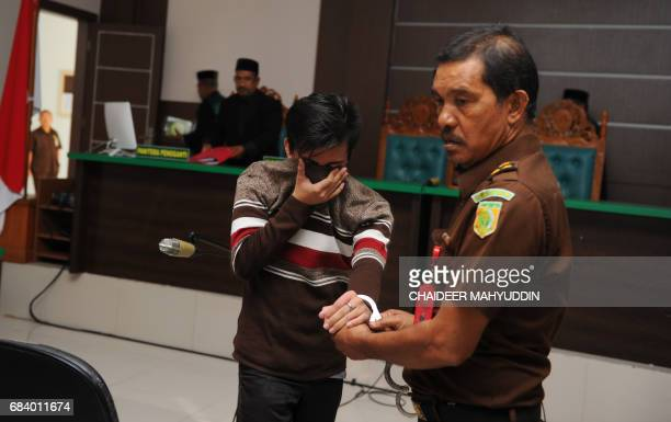 An Indonesian official escorts a man after his trial at a shariah court in Banda Aceh on May 17 2017 A sharia court on May 17 sentenced two men to be...