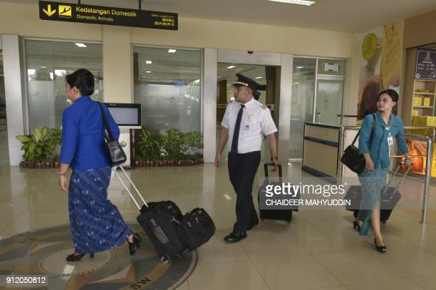 An Indonesian pilot and flight attendants arrive at the Sultan Iskandarmuda international airport in Aceh on January 30 2018 An Indonesian province...