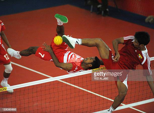 An Indonesian player kicks the ball as a player from Yanmar tries to defend during the Sepak Takraw men's team preliminary match at the 26th...