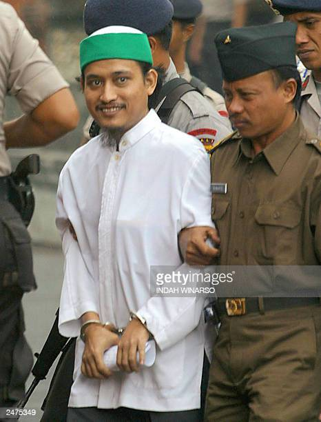 An Indonesian police escort Bali bombing terror key suspect Abdul Aziz alias Imam Samudra into the court room in DenpasarBali 10 July 2003 The Bali...