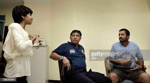 An Indonesian police investigator listens to Iranian survivor ten years old Athena Hardani annd her father Mohammad who were reunited for the first...
