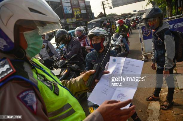 An Indonesian police officer inspects a document from a motorist heading toward the capital city of Jakarta in Bekasi West Java on May 29 amid travel...