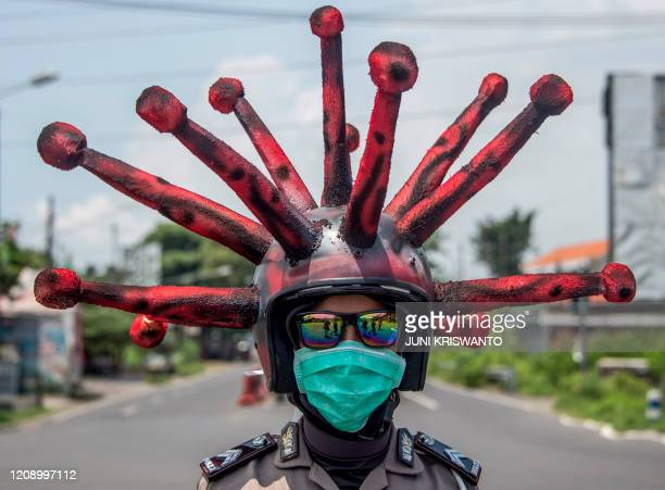TOPSHOT An Indonesian police officer wearing a Covid19 coronavirus themed helmet conducts a campaign and disinfects motorists' vehicles in Mojokerto...