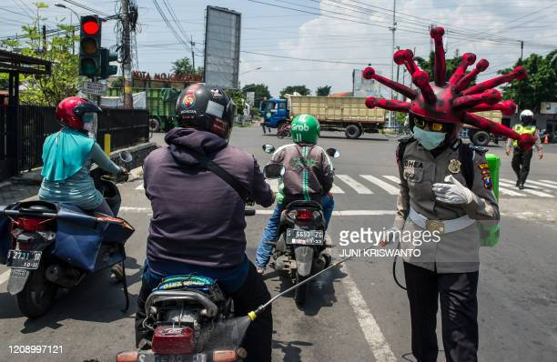 An Indonesian police officer wearing a Covid19 coronavirus themed helmet disinfects motorists' vehicles in Mojokerto East Java on April 3 2020