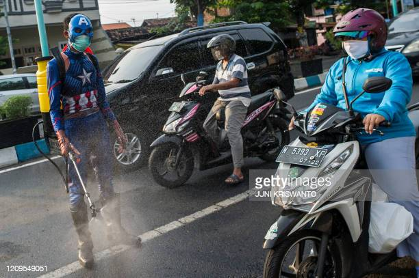 An Indonesian police officer wearing a superhero costume on the street disinfects motorists' vehicles in Pasuruan, East Java on April 9 amid concert...