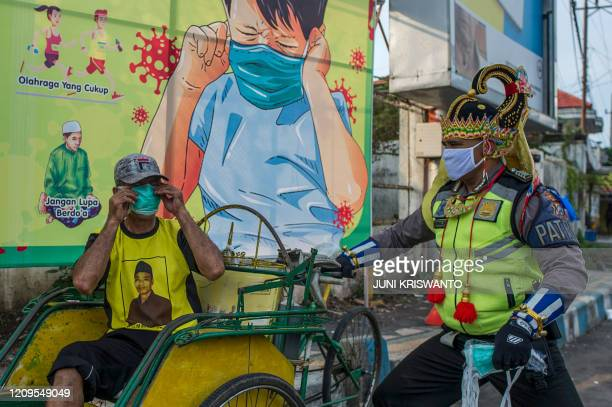 An Indonesian police officer wearing an Indonesian superhero costume on the street gives a face mask to a man in Pasuruan, East Java on April 9 amid...