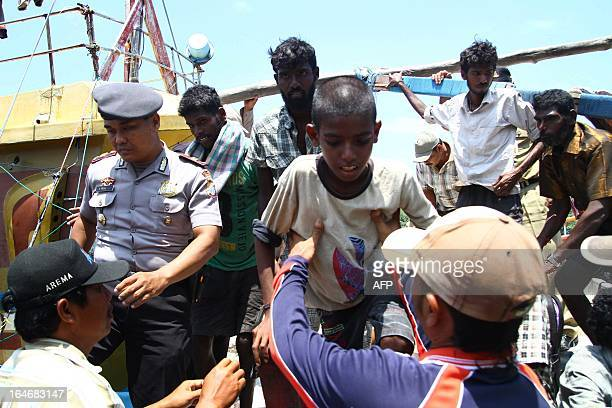 An Indonesian policeman escorts a group of 21 Sri Lankan asylum seekers on arrival at a port in Malang in East Java province on March 26 2013 after...
