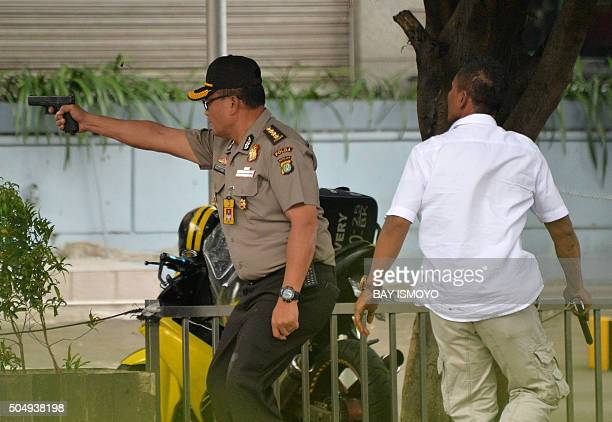 An Indonesian policeman fires his handgun towards suspects outside a cafe after a series of blasts hit the Indonesia capital Jakarta on January 14...