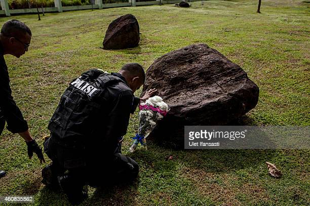 An indonesian policeman prays at mass grave to commemorate the tenth anniversary of the Boxing Day tsunami on December 26 2014 in Banda Aceh...