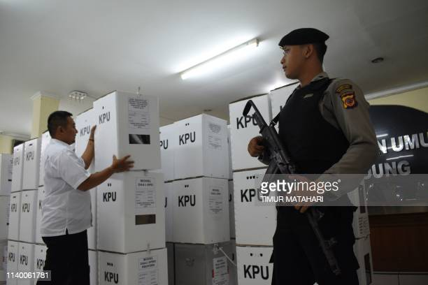 An Indonesian policeman stands guard as an official stacks boxes containing election results in Bandung West Java on April 29 2019 On April 17 the...