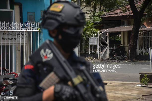 An Indonesian policeman stands guard at the site of an explosion outside a church in Makassar on March 28, 2021.